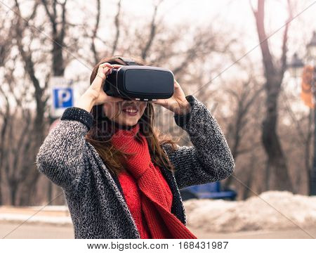 virtual reality headset VR glasses VR goggles - beautiful young girl with virtual reality headset or 3d glasses on the street interested by 360 image