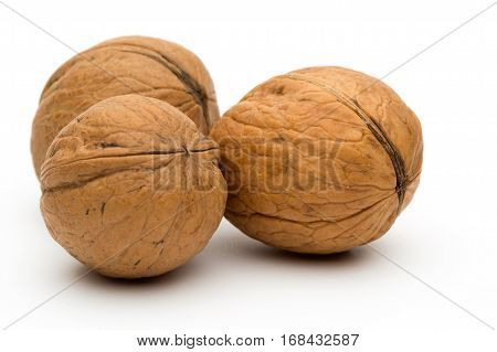 Three whole walnuts on a white background