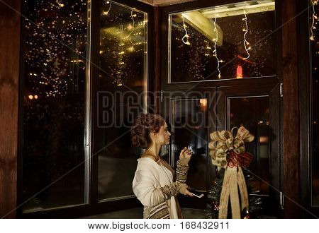 Beautiful girl with pretty hairstyle stands with phone in hands near the big wooden window in cozy, comfortable home, apartments. Cute girl look out window and wait for her husband, wait for call.