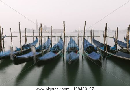 Gondolas the traditional flat-bottomed Venetian rowing boats at their moorings in San Marco Square at sunrise with the lagoon and the church of San Giorgio Maggiore in the background Venice Veneto Italy Europe (intentional motion blur)