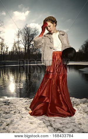 Nice woman in red dress posing in winter park
