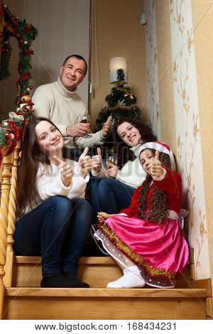 People family, christmas and adoption concept - happy mother, father and children hugging near a Christmas tree at home