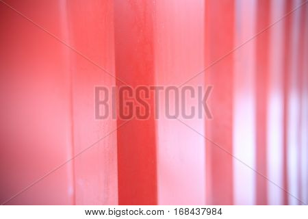 Red ribbed metal close up. Transportation container wall closeup. Red shiny background. Soft focus on red ribbed wall.