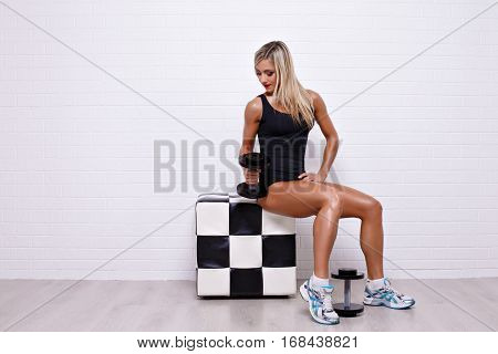 Side view of sexual blonde in bodysuit sitting on checkered poof and posing with dumbbells