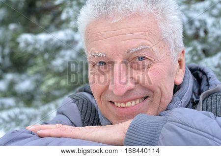 senior happy man posing outdoors in winter