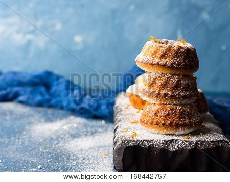 Mini bundt ring cakes with orange zest icing sugar on dark blue background and serving board. Holiday sweet food