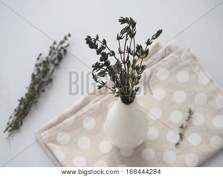 Bundle of thyme sprigs in small white vase over white wooden background. Selective focus on the sprigs.