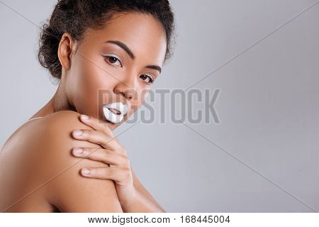 Bewitching glaze. Majestic young exotic girl posing with her hands crossed while wearing total white makeup accentuating her exquisite beauty