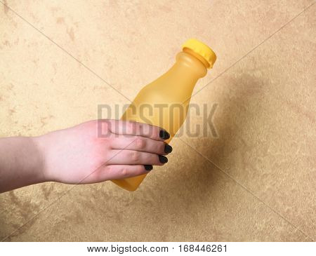 Yellow Glass Or Plastic Bottle In Hand On Beige Background