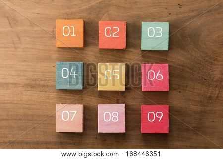 Index, menu or cover abstract back ground, with numbers and blank space for custom text, consisting of nine hand painted colored wooden cubes on grungy wooden background. pastel tone.
