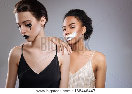 Monochromic concept. Thin delicate attractive women demonstrating a creative idea of a young makeup artist while working in a studio and posing for a professional photographer