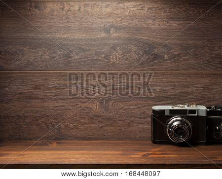 old camera at shelf wall wooden background texture