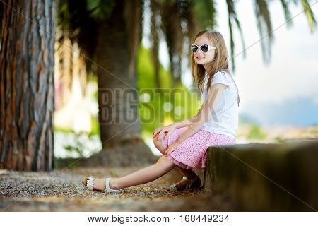 Cute Little Girl Wearing Sunglasses On A Shore Of Lake Garda In Toscolano-maderno, A Small Town And