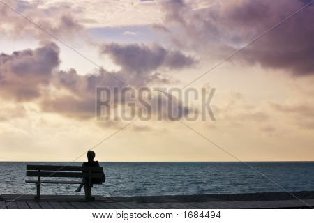woman sitting on bench looking out to sea sunset sky poster