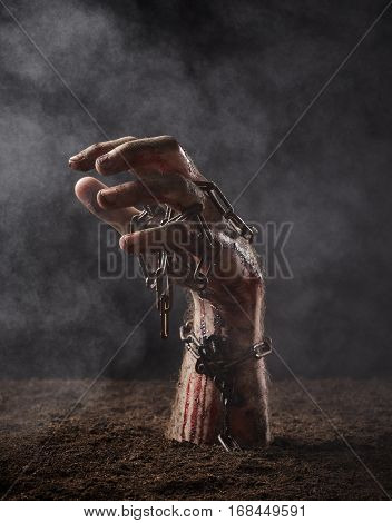 Hand of dead with chain climbs out of the ground