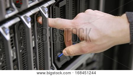 IT engineer or technician starts up a server in data rack. Working in enterprise datacenter.