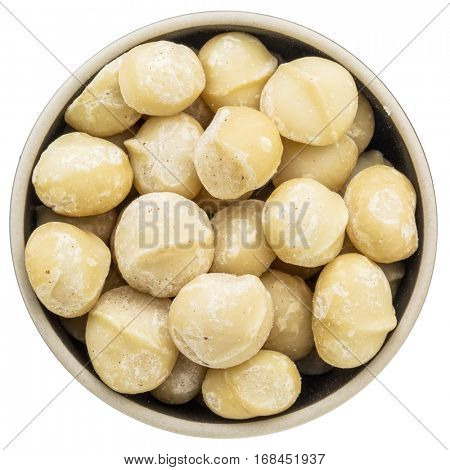 macadamia nuts in a ceramic bowl isolated on white