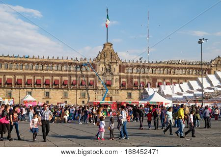 MEXICO CITY,MEXICO - DECEMBER 28,2016 : People at El Zocalo in Mexico City with the National Palace on the background