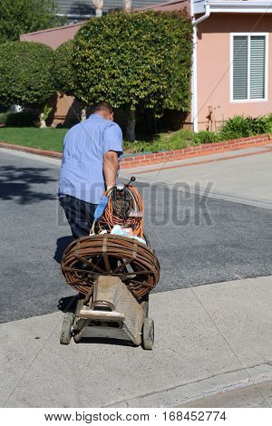 An Unidentifiable plumber unclogs a sewer drain with his Plumbing Snake and tools.