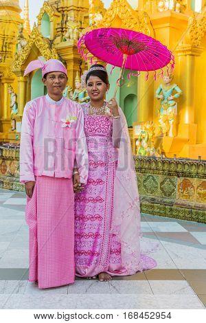 YANGON, MYANMAR -NOVEMBER 25, 2016 : Burmese bride and groom posing with traditional cosutmes Shwedagon Pagoda Yangon in Myanmar