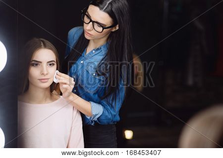 Preparation stage. Professional young makeup artist using a cotton pad and cleaning her clients skin while preparing to put on makeup