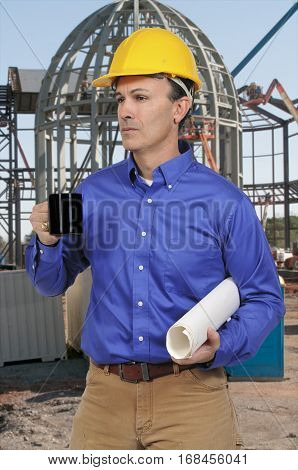 Handsome construction worker holding a cup of hot coffee