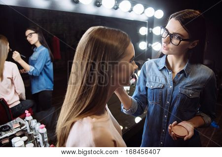 Natural look. Nice positive female makeup artist holding face powder and applying it on the cheek of her client with a makeup brush while standing in front of her