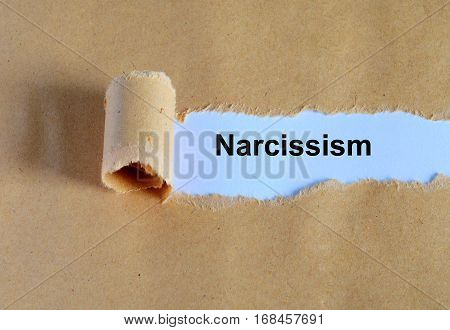 Narcissism Word Written Under Ripped And Torn Paper.