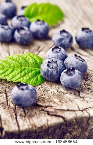 Blueberries with green leaves on wooden background