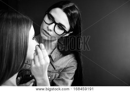 Professionalism and mastery. Professional skillful pleasant makeup artist standing in front of her client and putting on eyeshadow makeup while being at work