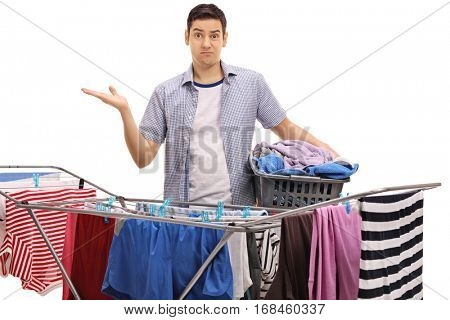 Confused guy holding a laundry basket and gesturing with his hand behind a clothing rack dryer isolated on white background