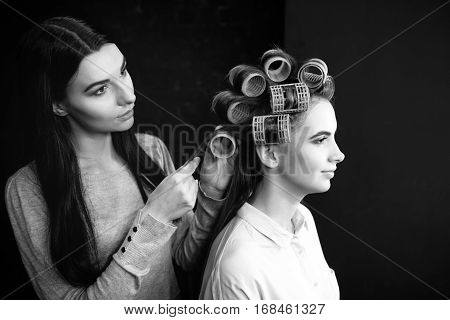 Wavy hair. Pleasant cute nice hairdresser working with hair roller and making a hairstyle for her client while standing behind her