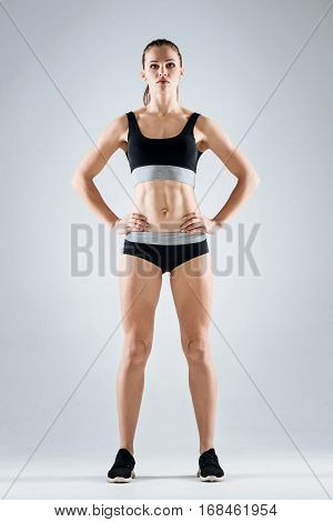 Keep fit. Young athletic pretty woman wearing sportswear while standing on grey background and posing.
