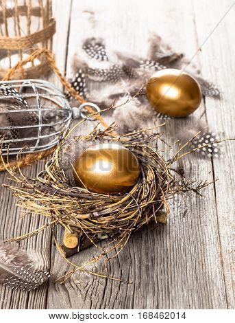 golden egg of chickens in nest on wooden background