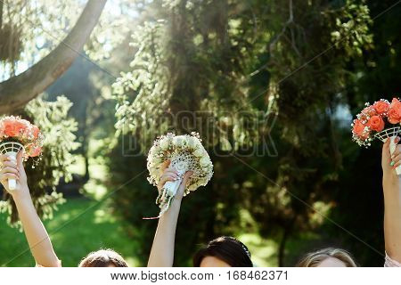 Happy Bride And Bridesmaids Showing Their Luxury Bouquets In Hands At Wedding Reception In Sunny Par