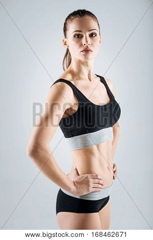 Keep moving. Satisfied active young woman wearing sportswear while standing on grey background and posing.