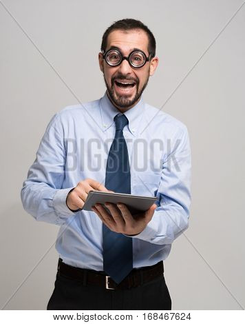 Nerdy businessman using his tablet