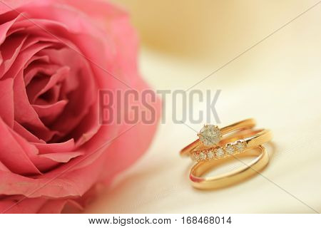 Diamond wedding rings and plain band and pink rose