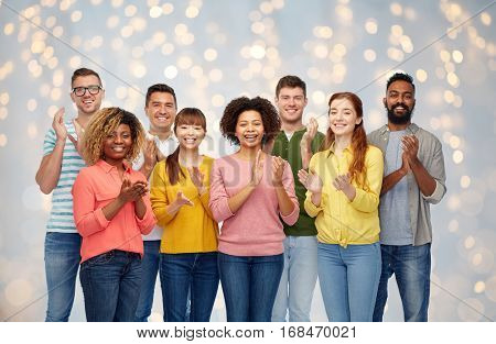 diversity, race, ethnicity and people concept - international group of happy smiling men and women applauding over holidays lights background