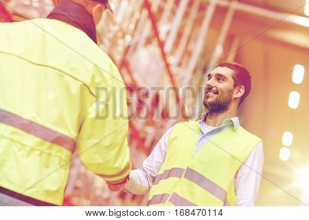 wholesale, logistic, people, agreement and export concept - manual worker and businessmen in reflective safety vests shaking hands and making deal at warehouse