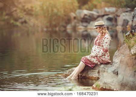 Pregnancy and Nature concept. New life. Pregnant woman resting on the river