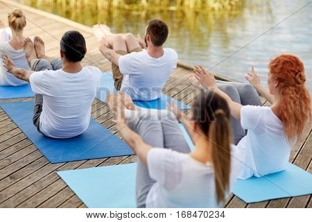 fitness, sport, yoga and healthy lifestyle concept - group of people making half-boat pose on river or lake berth