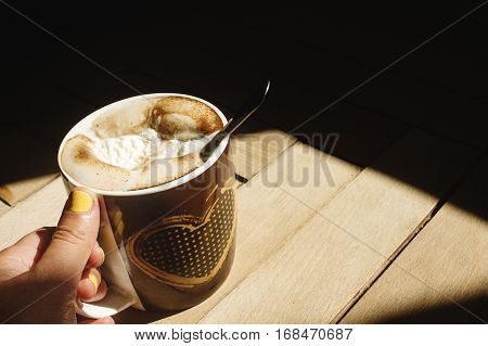 delicious aromatic brewed whipped with icecream coffee in a brown cup with a heart in a hand and sunlight in the morning on the background of a wood