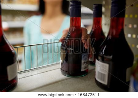 shopping, consumerism and people concept - woman taking bottle of vinegar or syrup from shelf at grocery