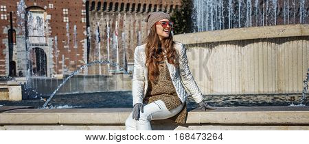 Happy Tourist Woman In Milan, Italy Sitting Near Fountain