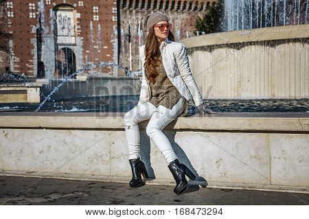 Woman Looking Into Distance While Sitting Near Fountain In Milan
