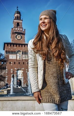 Rediscovering things everybody love in Milan. Portrait of smiling trendy tourist woman near Sforza Castle in Milan Italy