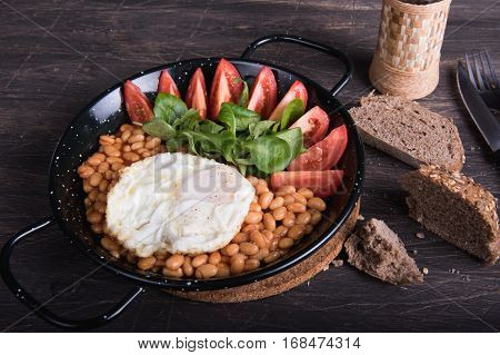 Beans eggs bread tomatoes in a black frying pan on a wooden background