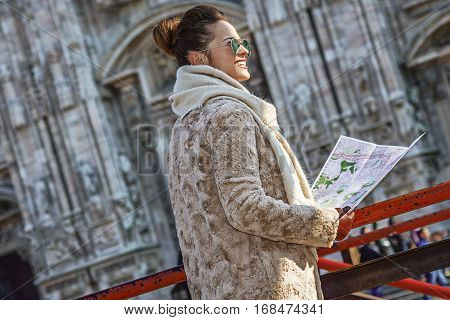 Rediscovering things everybody love in Milan. smiling young woman in fur coat and sunglasses in the front of Cathedral in Milan Italy with map looking into the distance poster