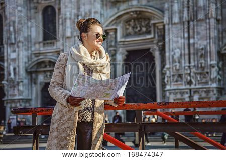 Rediscovering things everybody love in Milan. smiling young woman in fur coat and sunglasses in the front of Duomo in Milan Italy with map looking into the distance
